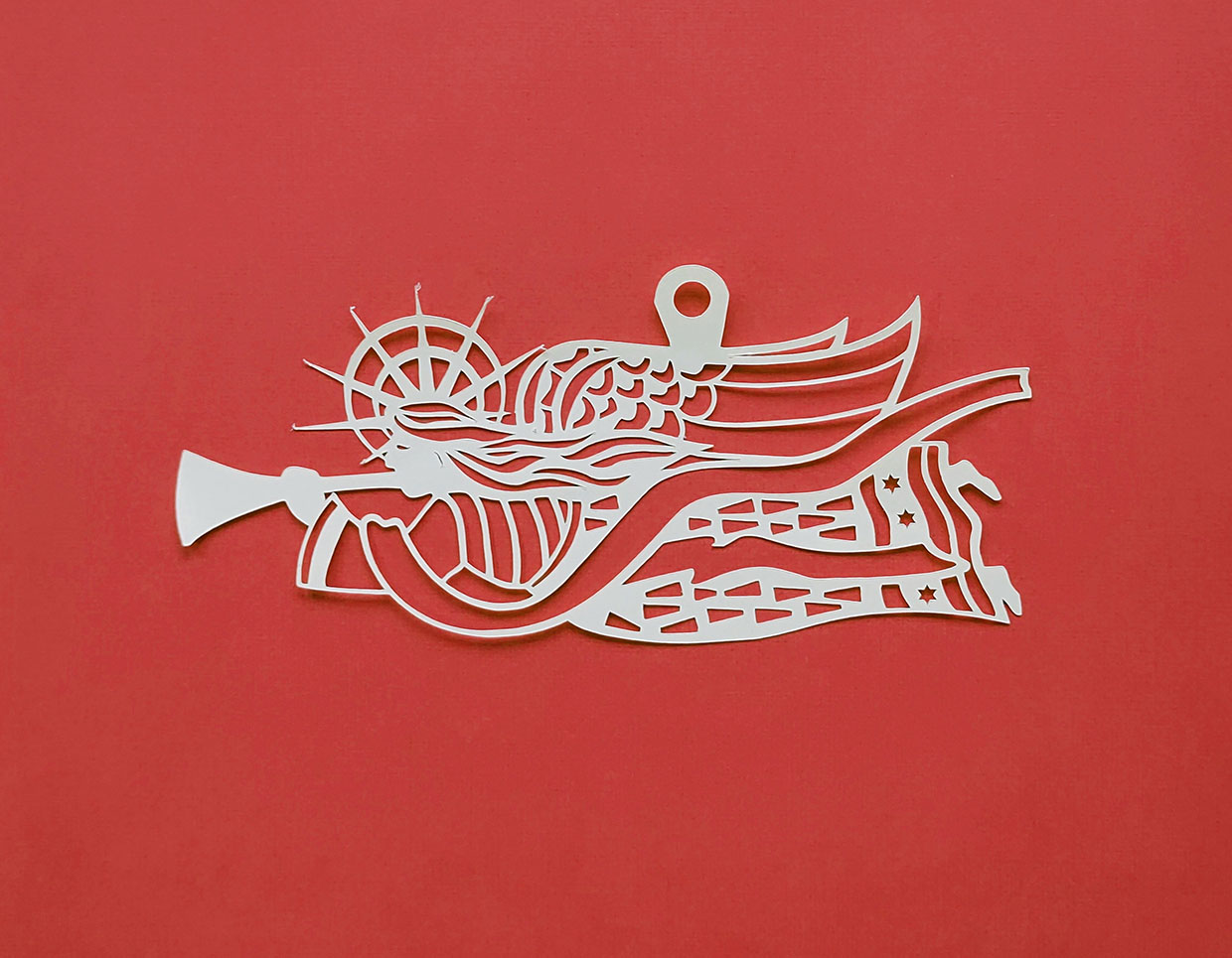 Paper cut of an angel flying playing the trumpet